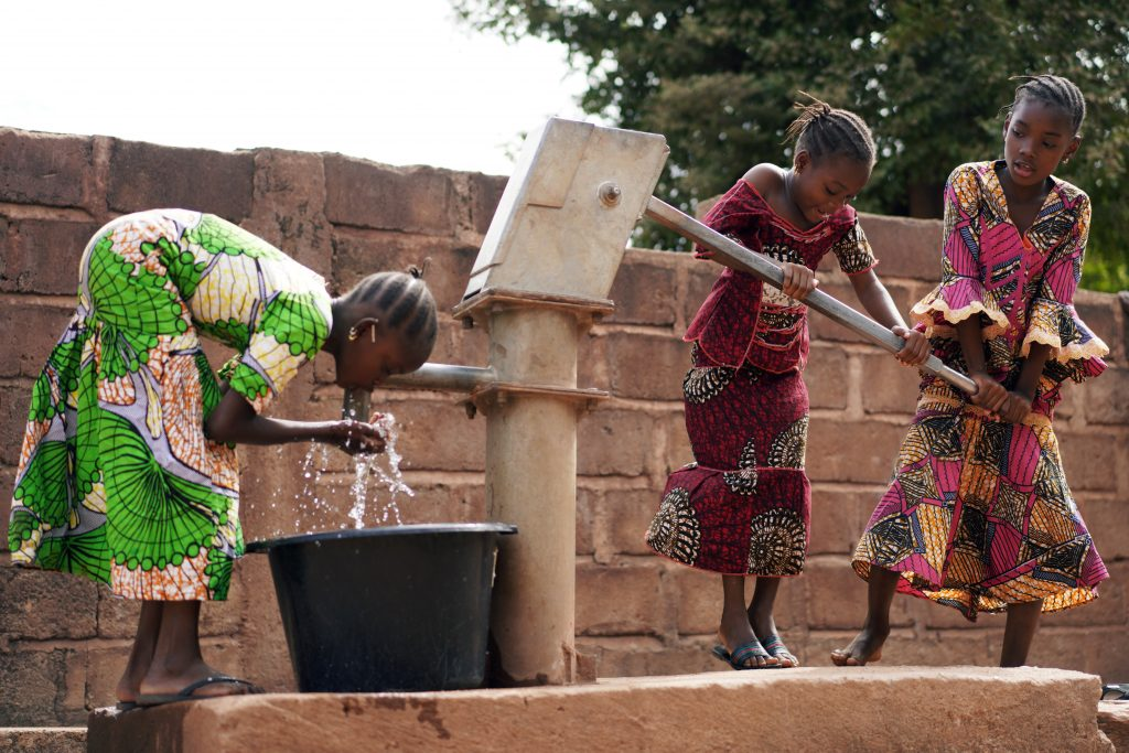 Three African Girls Filling Up Water Buckets At A Public